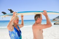 older-couple-with-surfboard